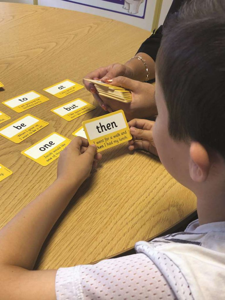 Photograph of young boy using PTS word cards on the 'How to support home reading' blog